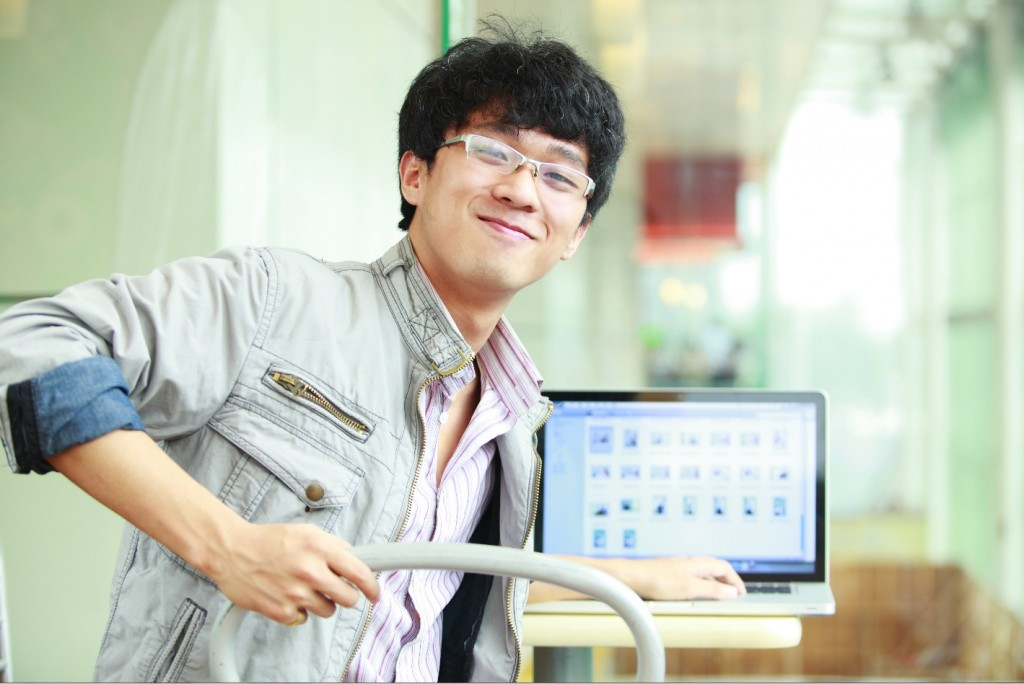 College student smiling at laptop