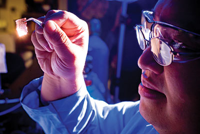 University at Buffalo researcher hold glowing chip in with lab tool
