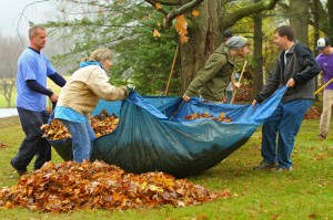 Alfred State's Outdoor Recreation Club Volunteers pick up leaves into a tarp