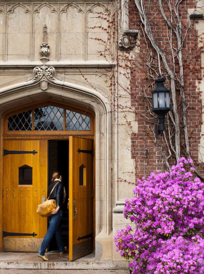Female students walks through wooden doors of building on SUNY Geneseo campus