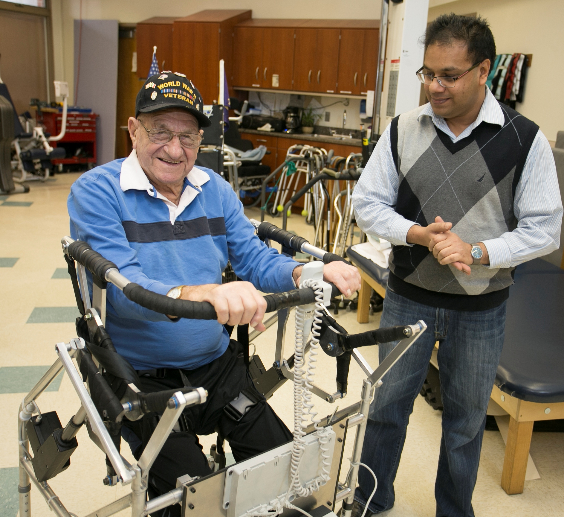 Stony Brook, NY: Long Island State Veterans Home: Anurag Purwar, Ph.D., Research Associate Professor, Department of Mechanical Engineering lets veteran Michael Geronimo test drive his mobile assist device.