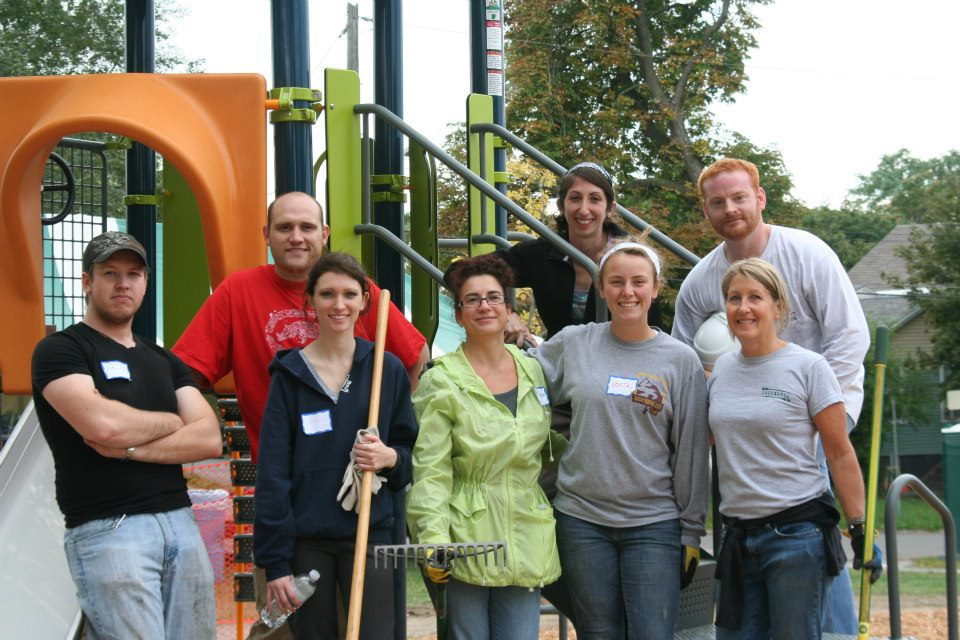 Onondaga Community College team members stand in front of a newly built playground