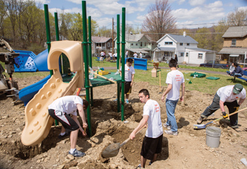 Binghamton School of Management students with the Pricewaterhouse Coopers Scholars cleaning up a playground's land