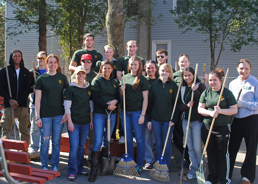 Herkimer County Community College students pose with tools at a park cleanup event