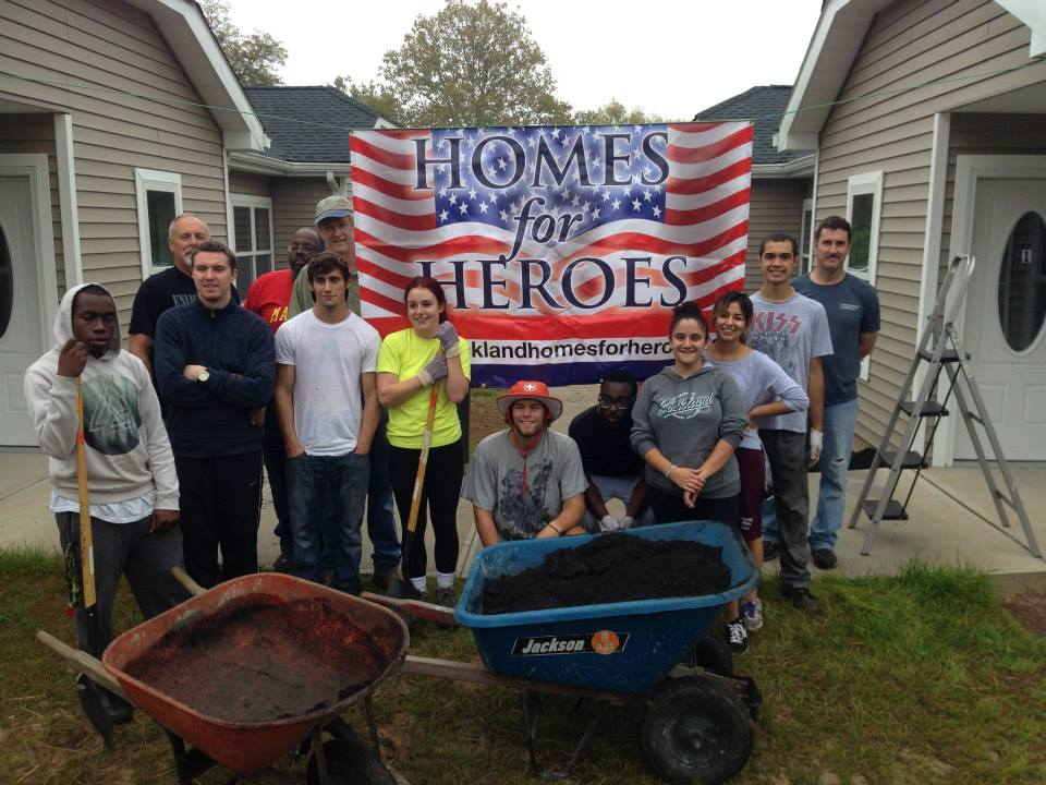 Rockland Community College students and faculty stand near newly constructed homes at Homes for Heroes
