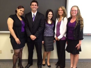 ACS students in business attire after presentation, in front of chalk board