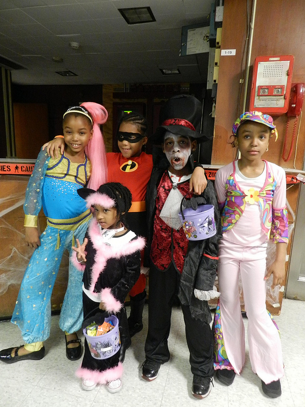 Students from PS 235 dressed in Halloween costumes with candy in hand.
