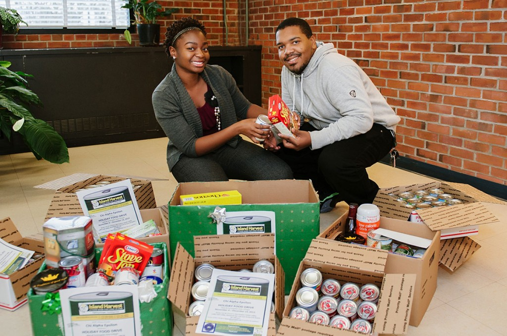Farmingdale State College students kneel behind boxes of donated food stuffs