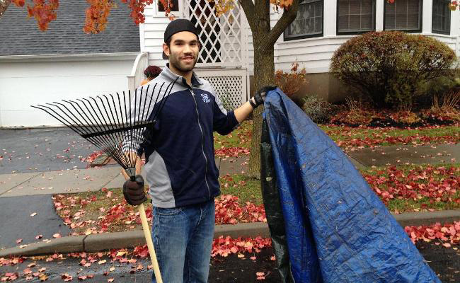 Male student athlete from SUNY Geneseo stands with rake and tarp in hand outside.