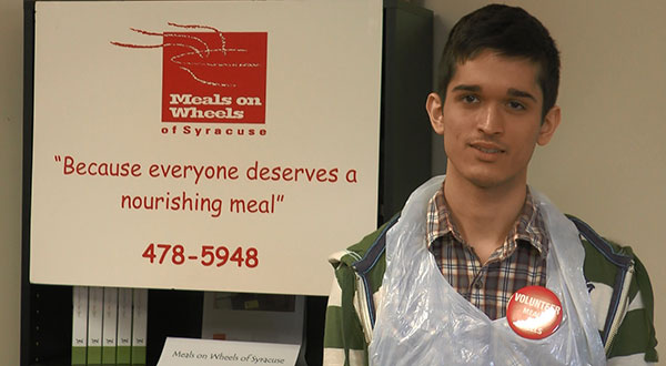 Anil Moore, student at Onondaga Community College stands before a Meals on Wheels display