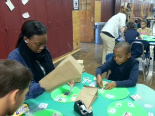 Monroe Community College student working with a second grade student at a craft table at the World of Inquiry School