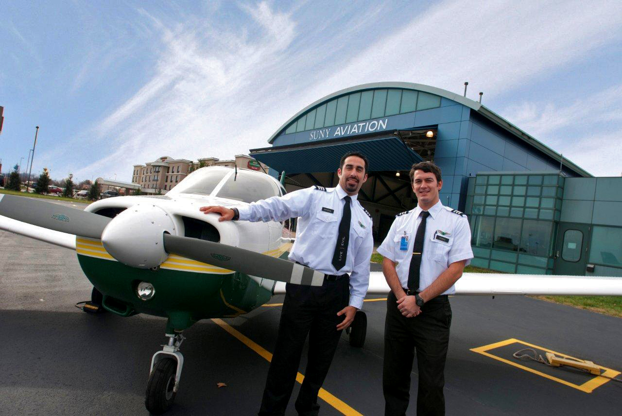 SUNY Farmingdale Plane with student pilots standing in front.