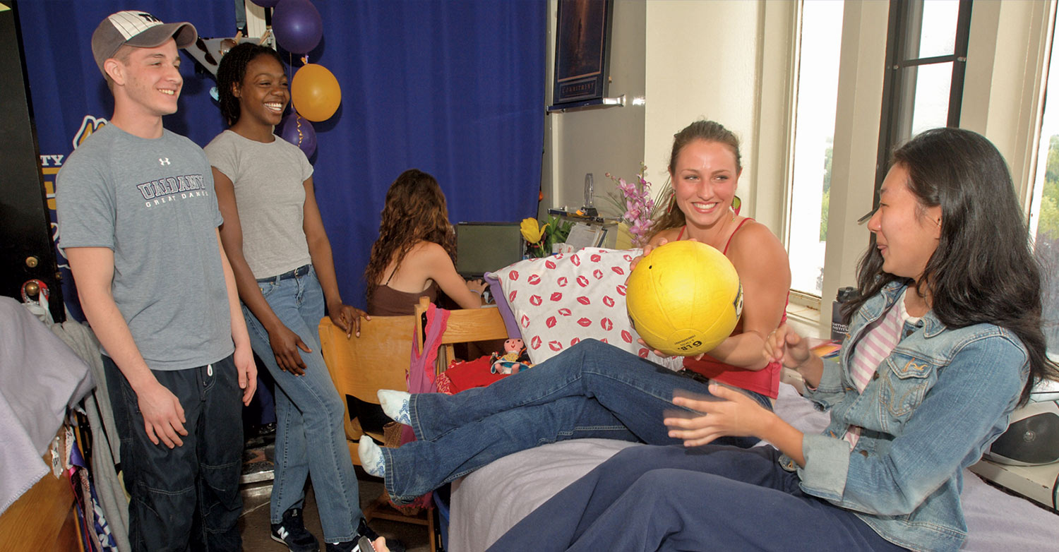 University at Albany students laugh in a dorm room.