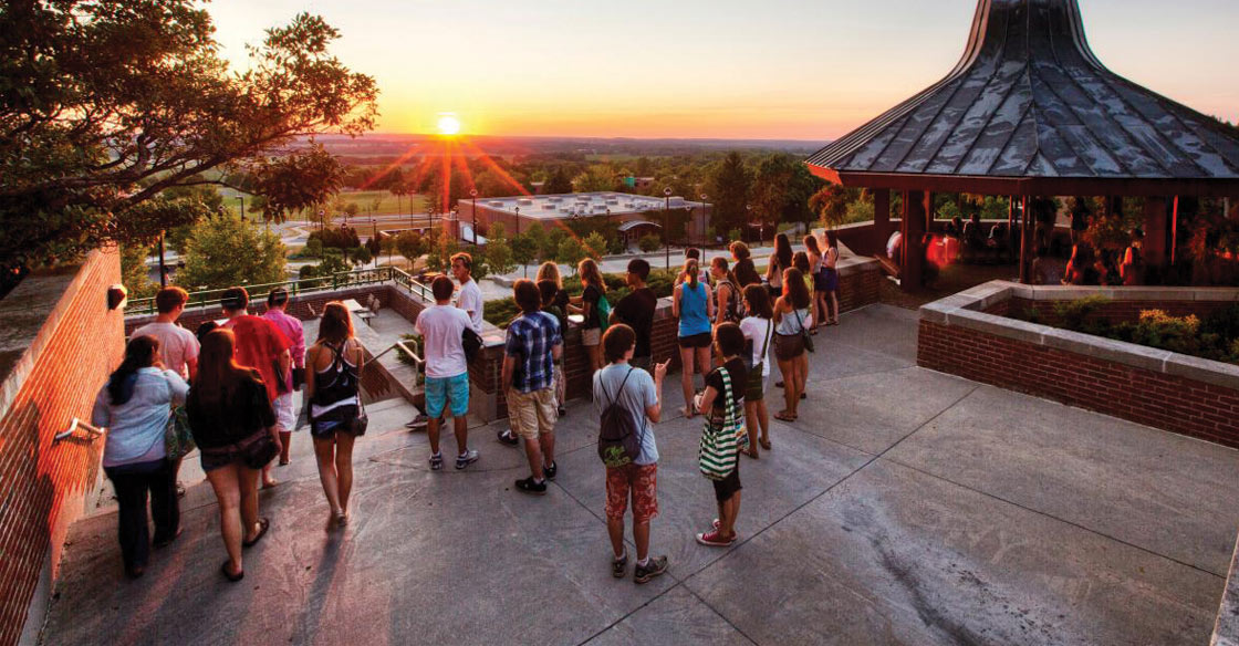 students gathered outdoors at Geneseo during sunset
