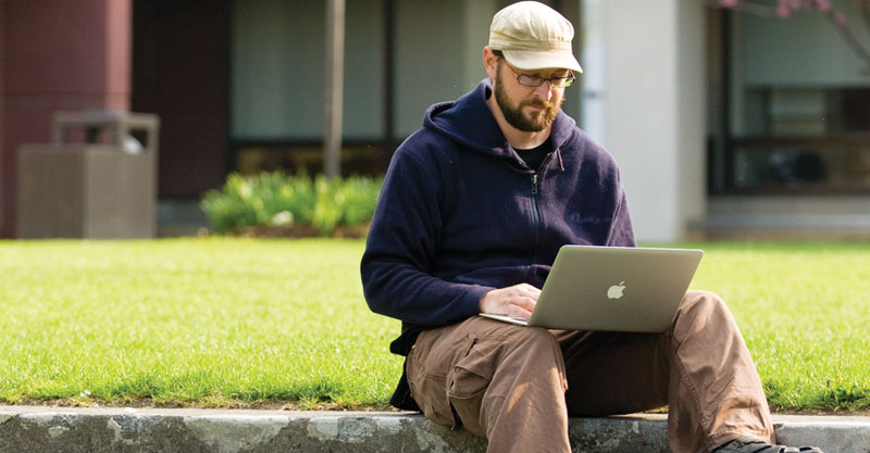 Student outside sitting on the grass with a laptop at Finger Lakes Community College