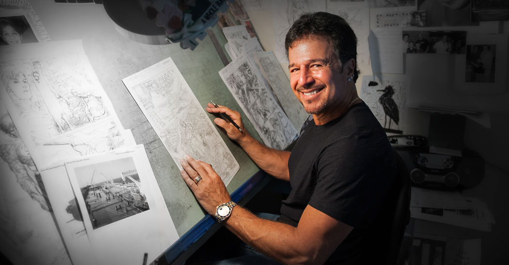 John Romita Jr, Farmingdale State College alumni, sits at a drawing table working on sketches of Superman for DC Comics.