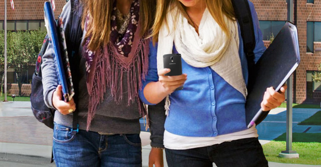 2 girls walking and looking at smartphone outside.