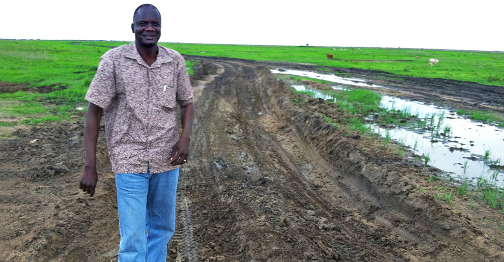 John Dau stands in a muddy dirt road, smiling.
