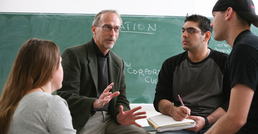 Plattsburgh students talk with professor at front of classroom.