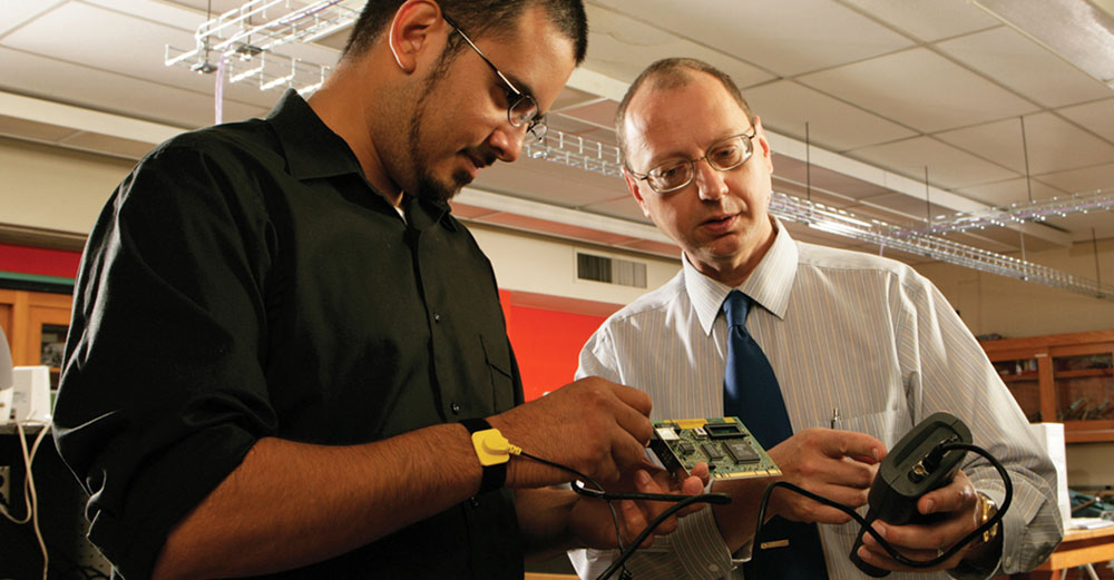 Genesee Community College student and teacher with building electronics