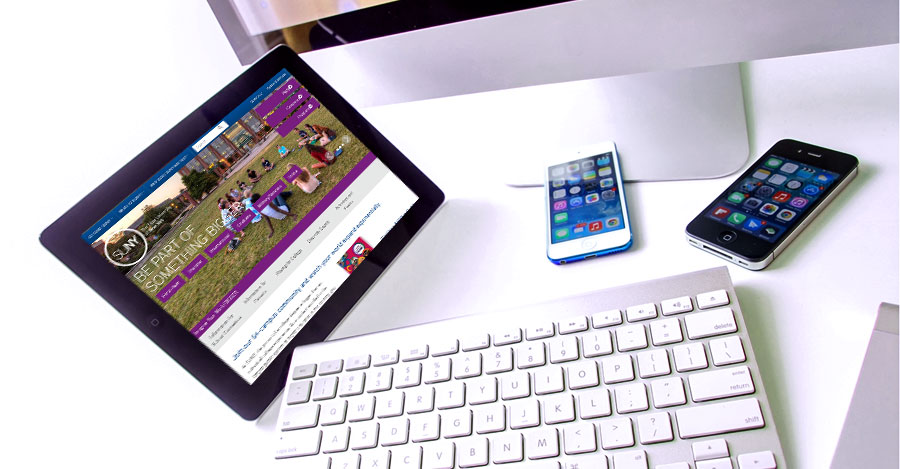 Apple iPad, iPhone and computer on white desk.