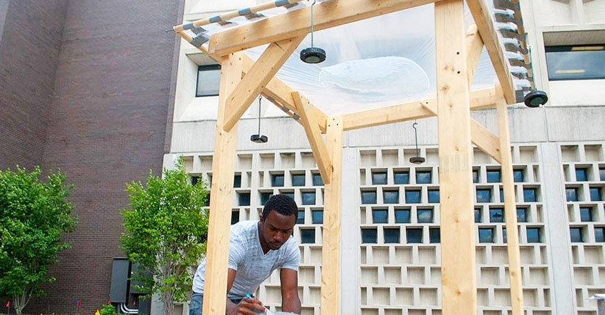 Deshawn Henry of the Univeristy at Buffalo uses his device made of wood, plastic sheeting and water, to disinfect water.