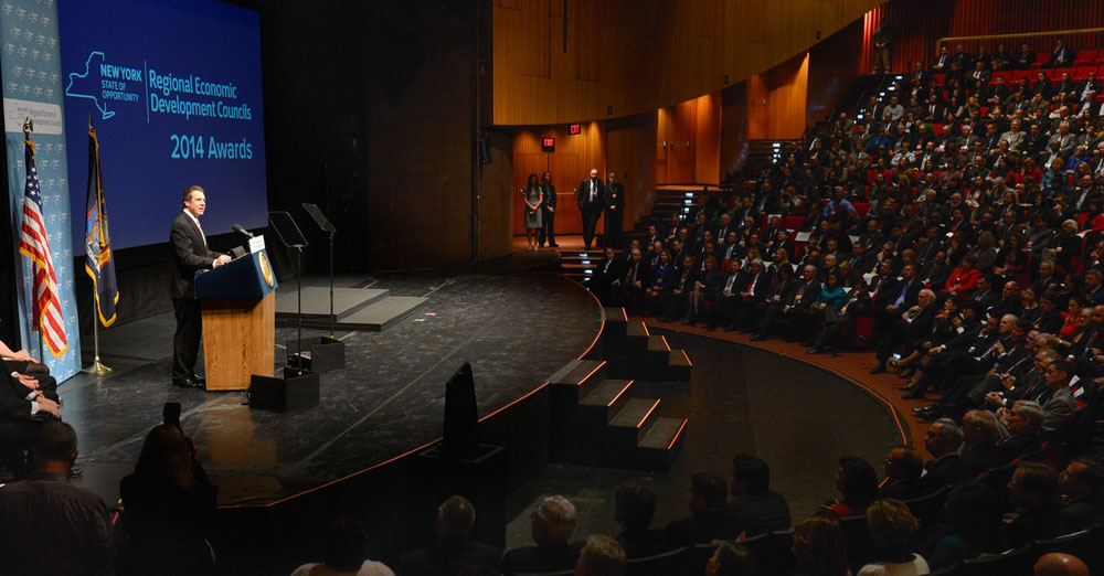 Governor Cuomo on stage announcing the 2014 REDC Awards