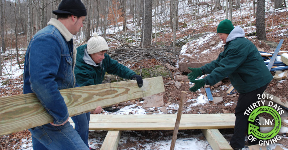 SUNY Delhi students prepare wood to build a house with Habitat for Humanity.