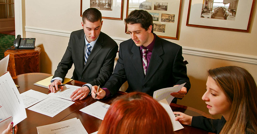 SUNY Delhi business students at a conference table in business dress.