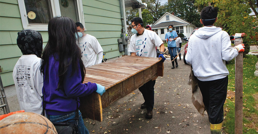 Binghamton University students doing community service by fixing a house.