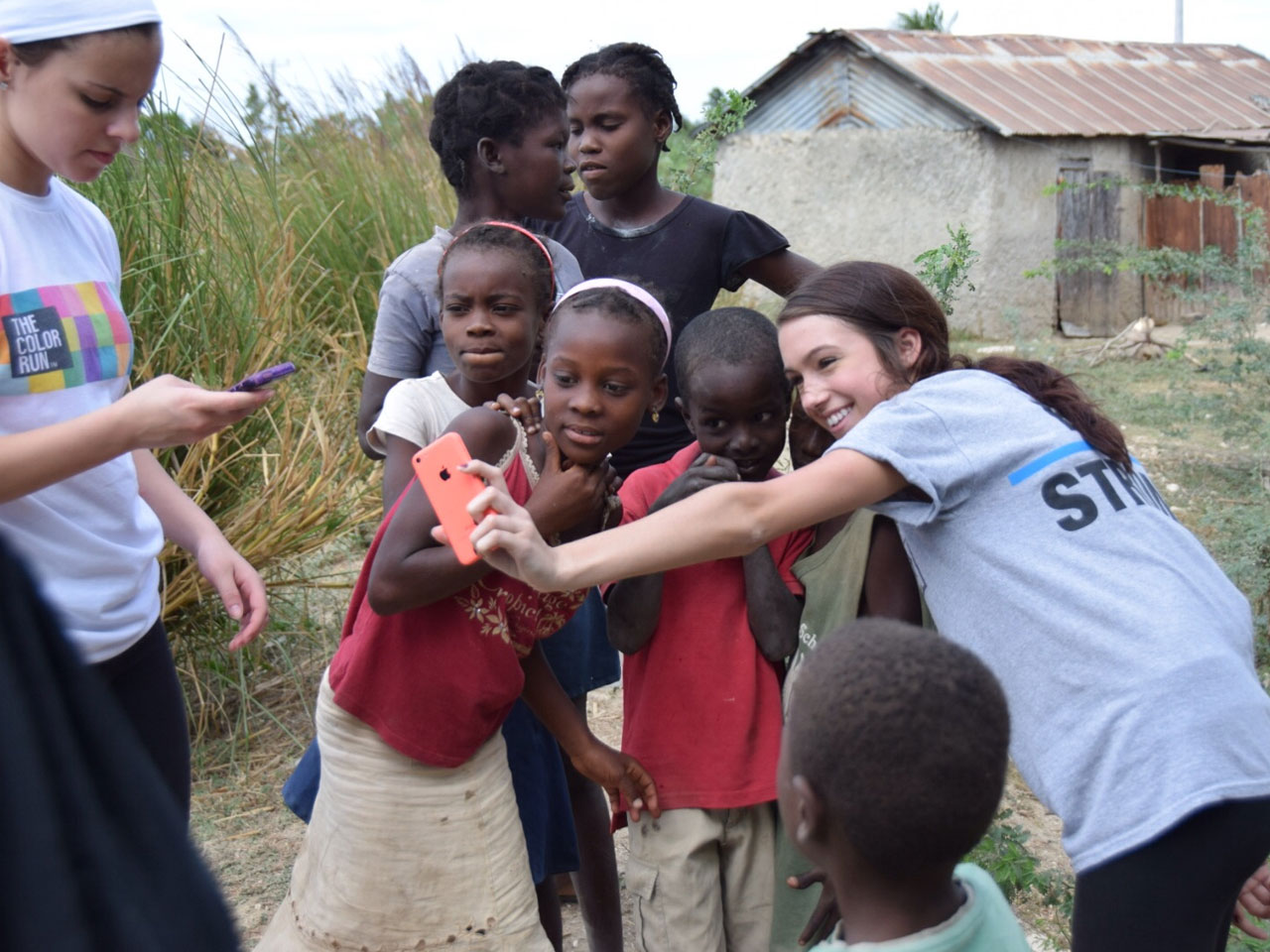 SUNY Broome female student poses for selfie with Haitian children in Haiti.