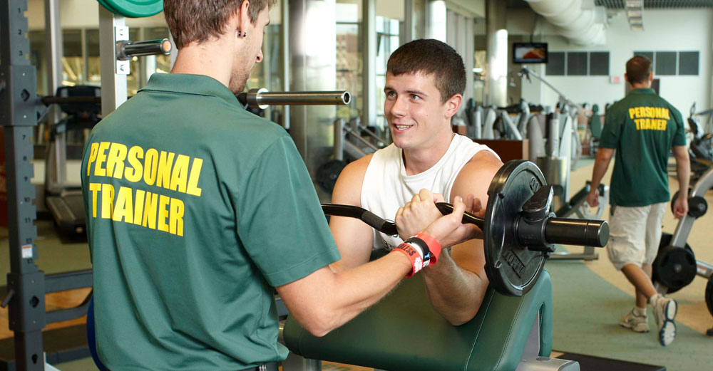 Brockport student works out with trainer in school gym.