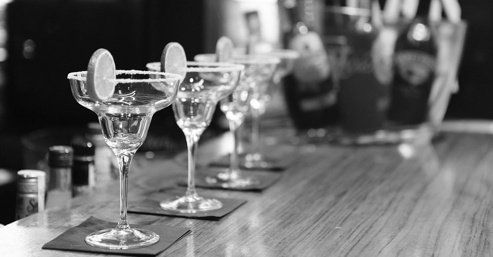 cocktail glasses on bar in black and white