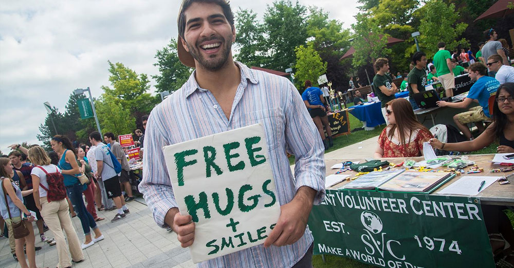 One student looks to spread joy around campus with a sign saying Free Hugs and Smiles..