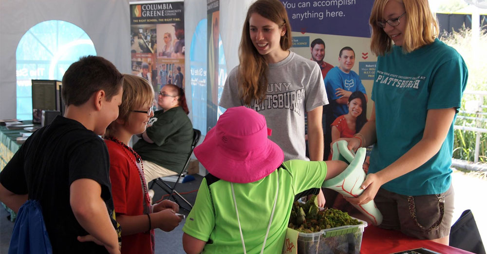 Plattsburgh ecology students Kaitlyn Mroczka and Kinsey Irving teach the next generation of science students about pitcher plants.