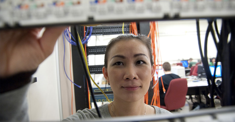 Monroe Community College female stands behind partition working with wires near computer server.