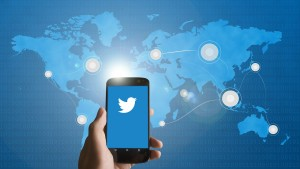 cellphone with twitter logo in front of map of the world.