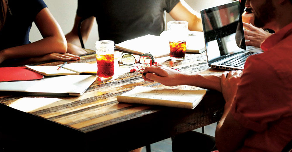 3 people at a table with notebooks and drinks having an informal business brainstorm session.