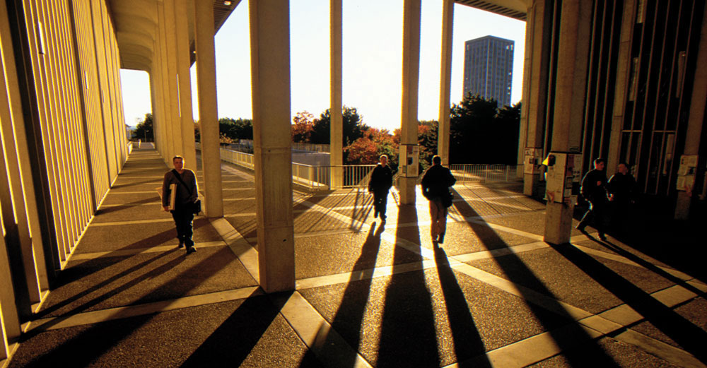 Students walking on the University at Albany campus at twilight.