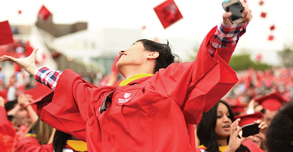 Stony Brook University graduate cheers with classmates at commencement.