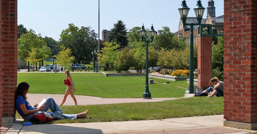 Girl reads on SUNY Geneseo campus in daylight sun.