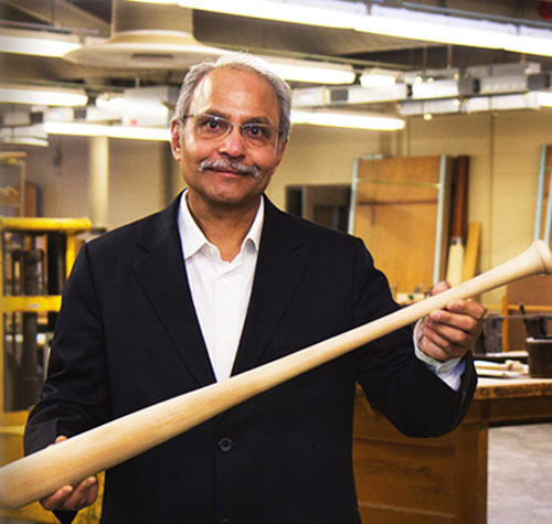 Prakash Suthar of Windsor Wood USA stands with baseball bat in hand inside factory