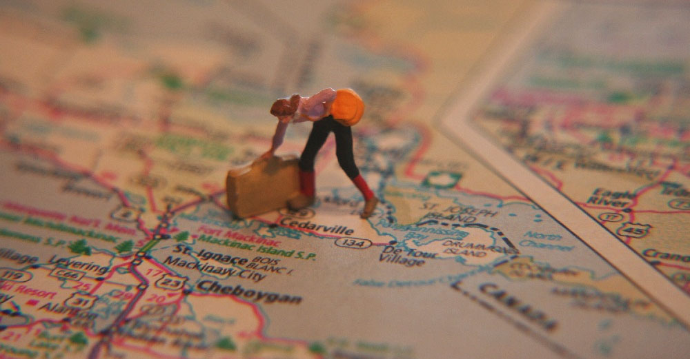 road map with little rubber person figurine with suitcase.
