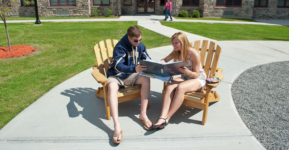 Students at SUNY Canton read in adirondack chairs in the sun outside.