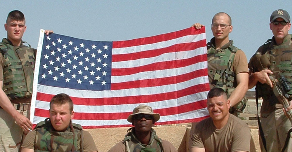Brian Huskie and infantry men partners with American Flag in Iraq.