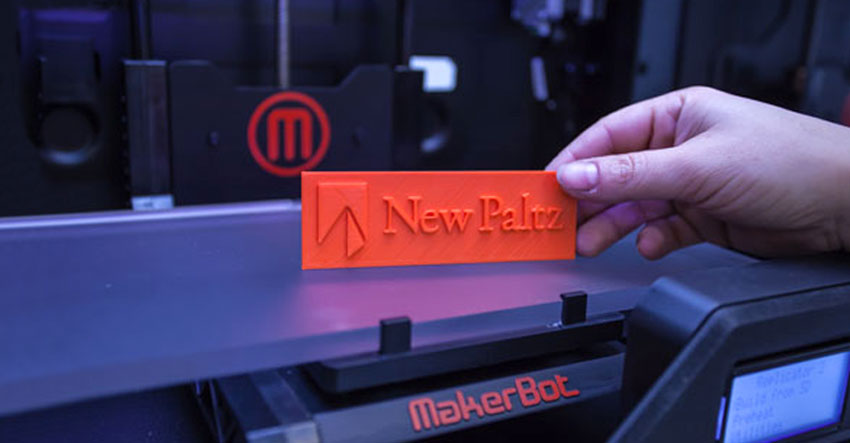 A 3D printed orange tag with SUNY New Paltz logo on it in front of MakerBot 3D printer.
