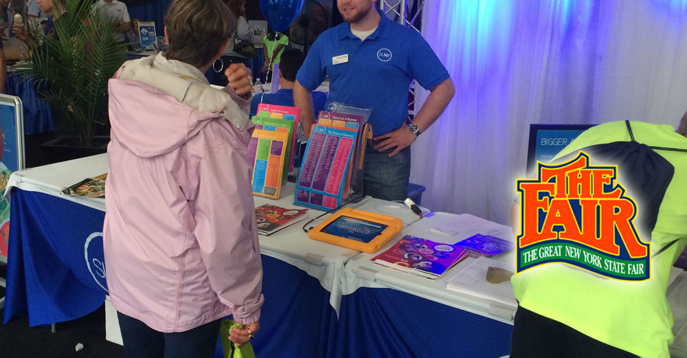 SUNY representative speaks to visitors at the 2014 NY State Fair.