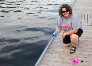 Professor Barbara Brabetz of SUNY Cobleskill knees on a dock as she samples water from the Mohawk River.