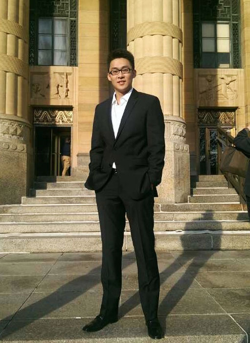 Oscar Xu stands outside in a suit.