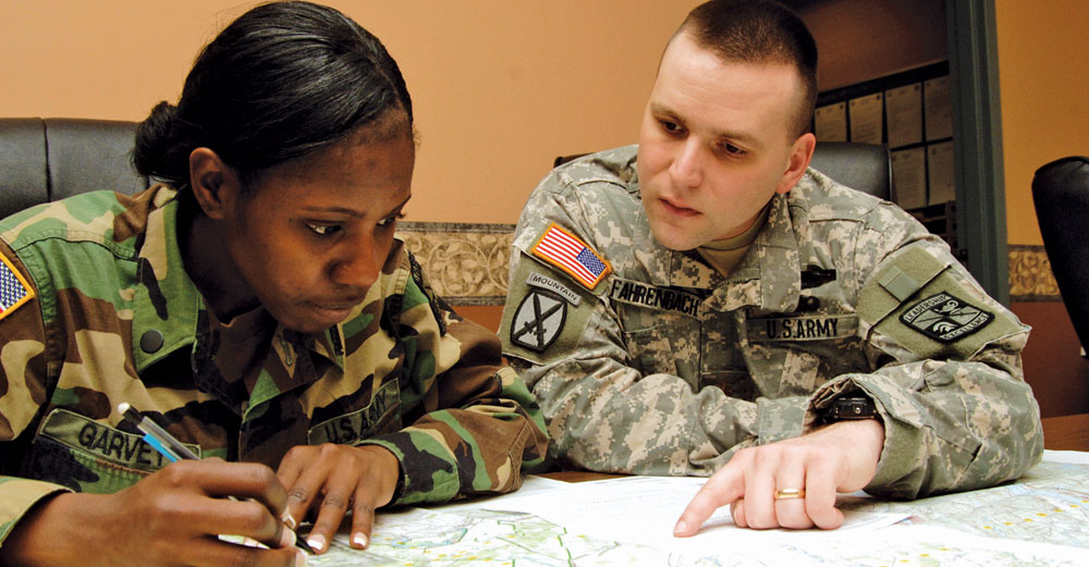 Male and female ROTC students at Brockport do homework together at a table.